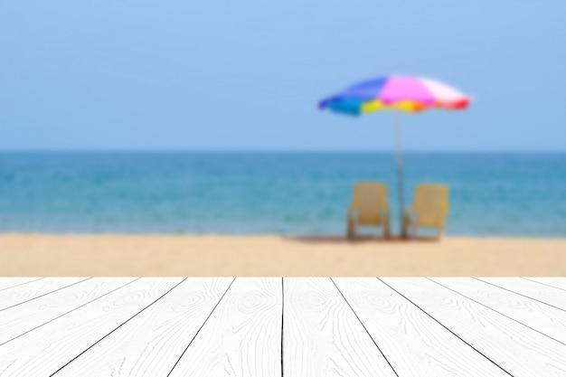Mesa de mármore branca vazia sobre o mar azul do borrão e o céu no fundo do verão
