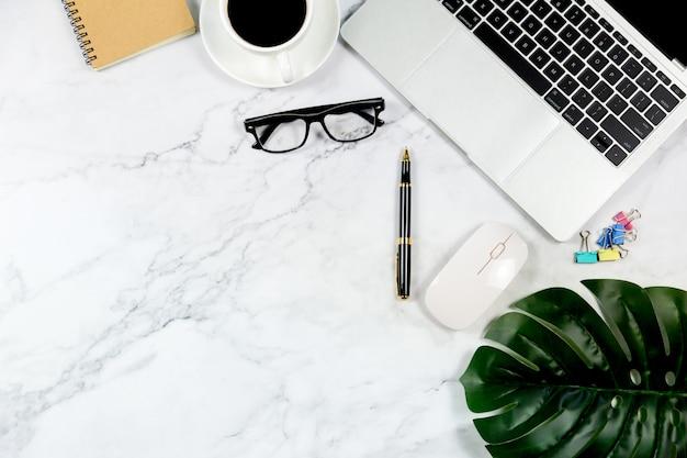 Mesa de mármore branco com caderno em branco e outros materiais de escritório