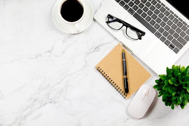 Mesa de mármore branco com caderno em branco.