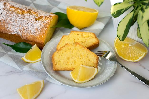 Mesa de mármore com um pedaço de torta de limão no prato, bolo caseiro de pão de laranja recém-assado no pano de prato, frutas cítricas e planta da casa.