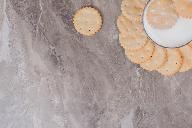 Mesa de mármore copo de leite e biscoitos.