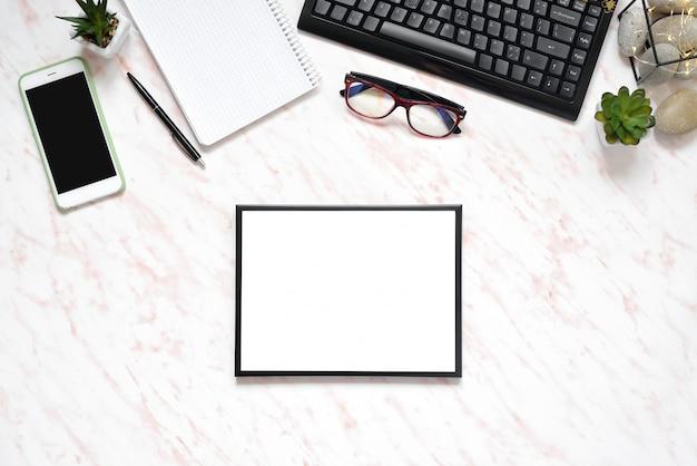Mesa de mármore plana leigo escritório com telefone, teclado e notebook, quadro para o fundo do espaço de texto