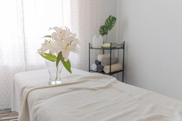 Mesa de massagem com lençóis brancos