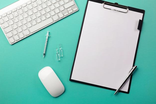 Mesa de médicos com tablet, caneta, teclado, seringa e ampolas