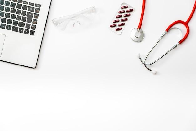 Mesa de médicos vista superior com estetoscópio e laptop.