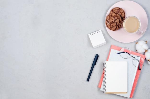 Mesa de mesa cinza local de trabalho com notebooks, espaço em branco vazio, suprimentos, copos e xícara de café.