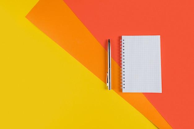 Mesa de mesa de escritório amarelo e laranja com caderno em branco e outros materiais de escritório. vista superior com espaço de cópia, postura plana.