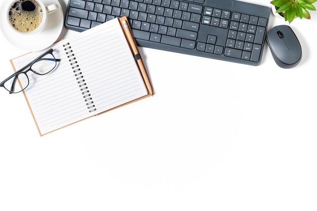 Mesa de mesa de escritório branca, caderno em branco com laptop e café preto isolado no fundo branco. vista superior com espaço de cópia, camada plana