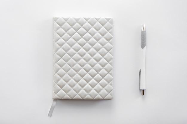 Mesa de mesa de escritório branca com um caderno e caneta sobre ela