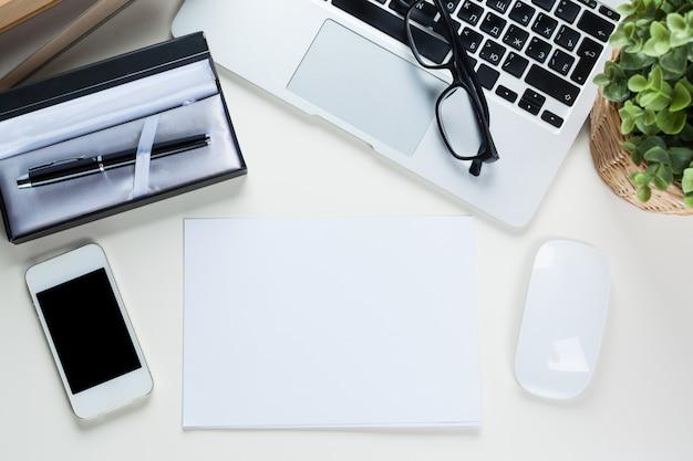 Mesa de mesa de escritório branco com documento de folha de página em branco. vista do topo
