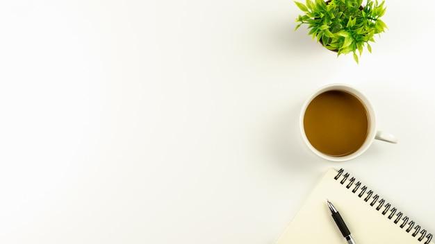 Mesa de mesa de escritório branco com uma xícara de café e uma caneta no caderno em branco