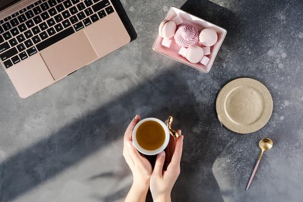 Mesa de mesa de escritório cinza moderno com laptop, outros suprimentos com uma xícara de chá.