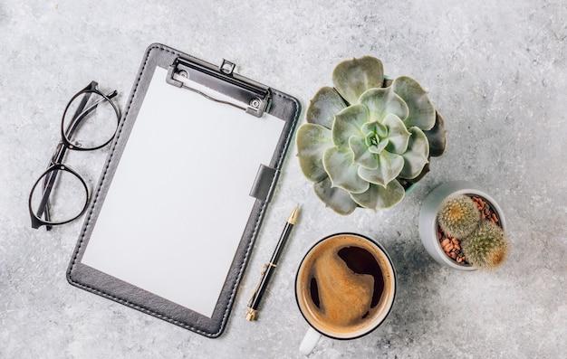 Mesa de mesa de escritório com computador, suprimentos, xícara de café e cacto