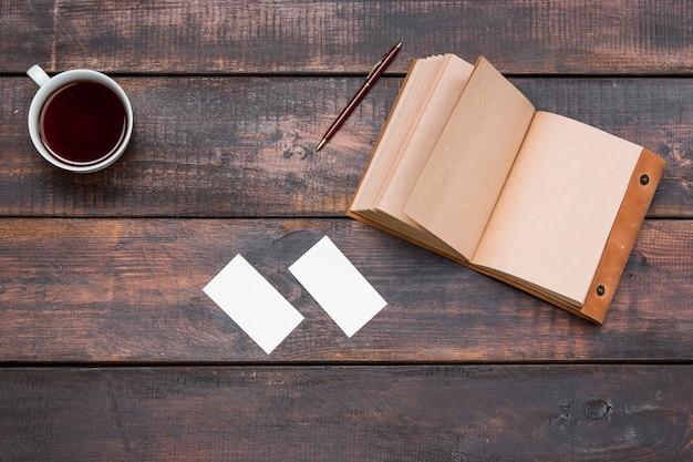 Mesa de mesa de escritório com copo, caderno, cartões na mesa de madeira