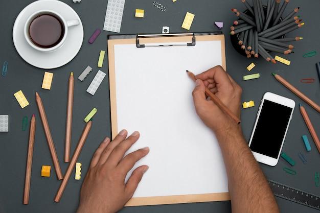 Mesa de mesa de escritório com lápis, suprimentos, telefone e mãos masculinas