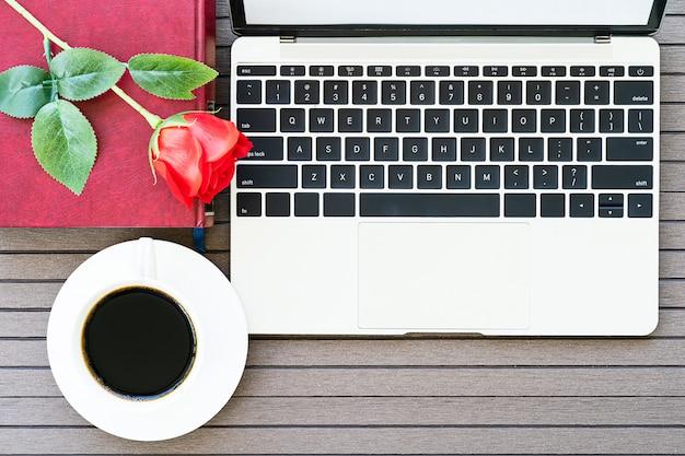 Mesa de mesa de escritório com laptop, notebook, xícara de café, rosa vermelha