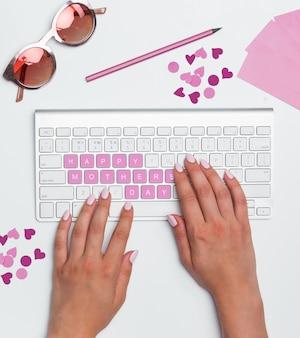 Mesa de mesa de escritório com mãos femininas, computador, suprimentos, flores. vista superior com conceito de feliz dia das mães