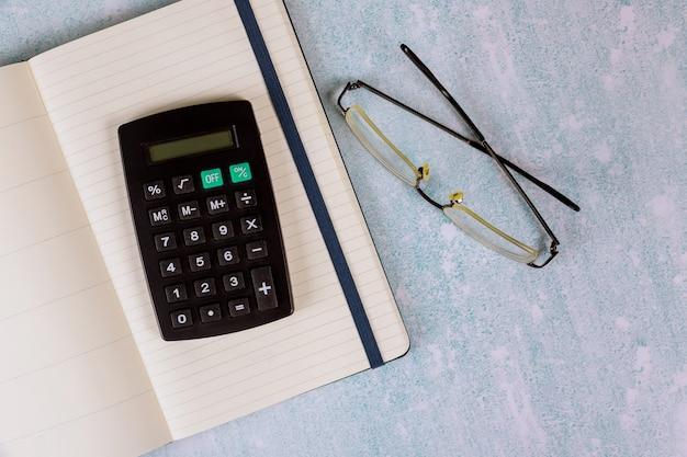 Mesa de mesa de escritório com óculos no notebook, calculadora
