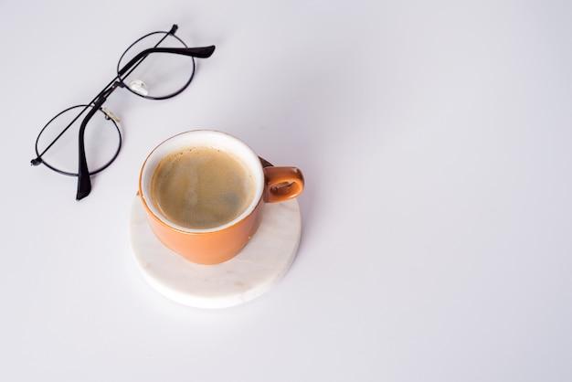 Mesa de mesa de escritório com xícara de café, caneta e óculos. vista superior com espaço de cópia