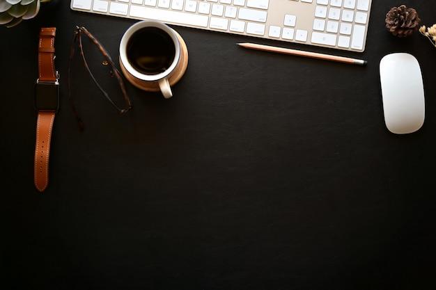 Mesa de mesa de escritório de couro escuro com computador desktop, notebook aberto, caneca de café