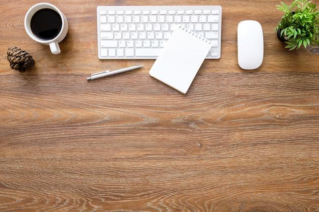 Mesa de mesa de escritório de madeira com teclado de computador com o mouse, caderno em branco, xícara de café e suprimentos.