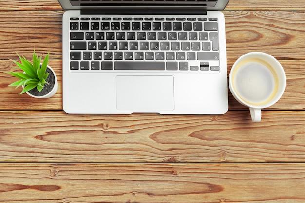 Mesa de mesa de escritório de madeira e equipamentos para trabalhar com café preto em vista de ângulo