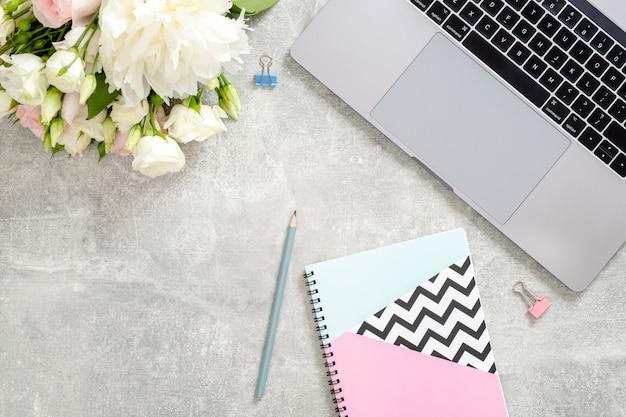 Mesa de mesa de escritório de mulher com computador portátil, flores, bloco de notas elegante diário, artigos de papelaria em pedra de concreto