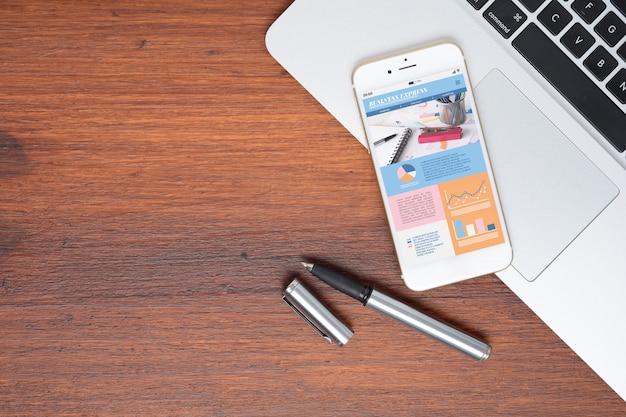 Mesa de mesa de escritório e telefone smartphone com informações gráficas sobre o crescimento da empresa