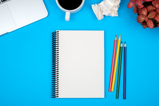 Mesa de mesa de escritório moderno com página de laptop e caderno em branco