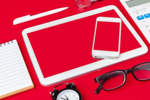 Mesa de mesa de escritório vermelho com caderno em branco, teclado e suprimentos.