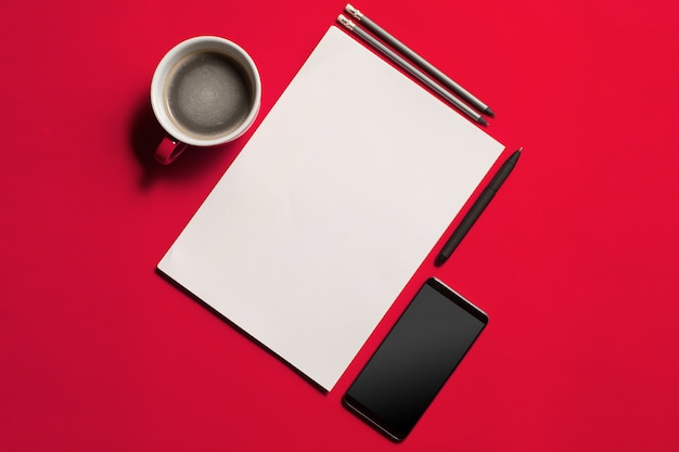 Mesa de mesa de escritório vermelho moderno com smartphone e xícara de café.