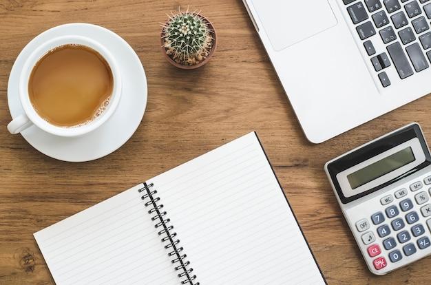 Mesa de mesa de madeira com notebook, laptop, calculadora, cactos e xícara de café.