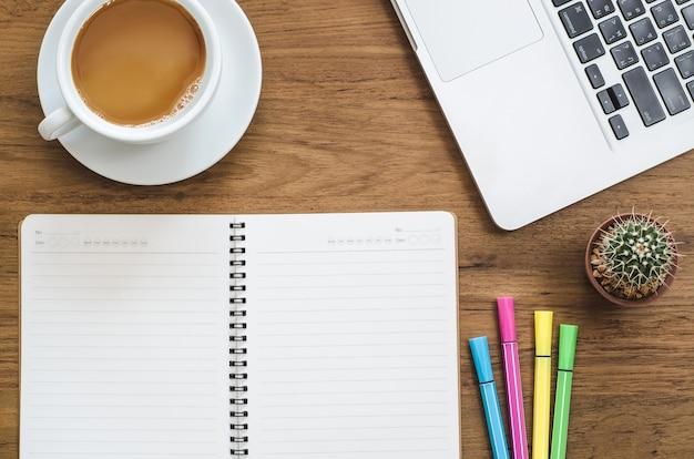 Mesa de mesa de madeira com notebook, laptop, caneta de cores, cactos e xícara de café. vista superior com espaço de cópia.