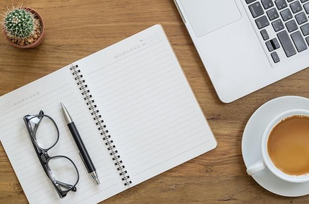 Mesa de mesa de madeira com notebook, laptop, caneta, óculos, cactos e xícara de café. vista superior com espaço de cópia