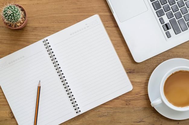 Mesa de mesa de madeira com notebook, laptop, lápis, cactos e xícara de café. vista superior com espaço de cópia.
