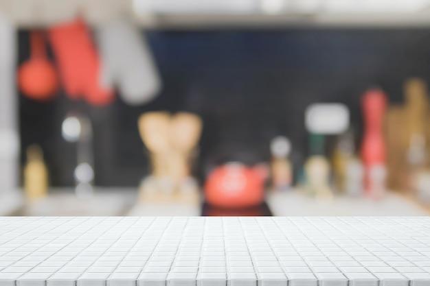 Mesa de mesa de mosaico de cerâmica branca vazia e fundo de cozinha embaçado