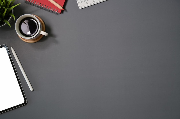 Mesa de mesa escura do escritório com computador, suprimentos, tablet e caneca de café.