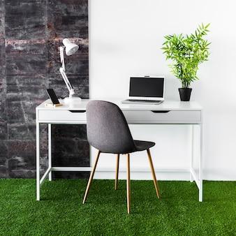 Mesa de metal com laptop e cadeira