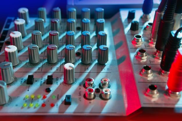 Mesa de música mixer de áudio sob luzes coloridas