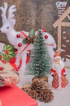 Mesa de natal com veado de brinquedo, pinheiro e papai noel.