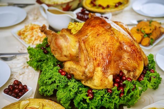 Mesa de natal servida com peru, decorada com couve e cranberry. conceito de feriado do ano novo.