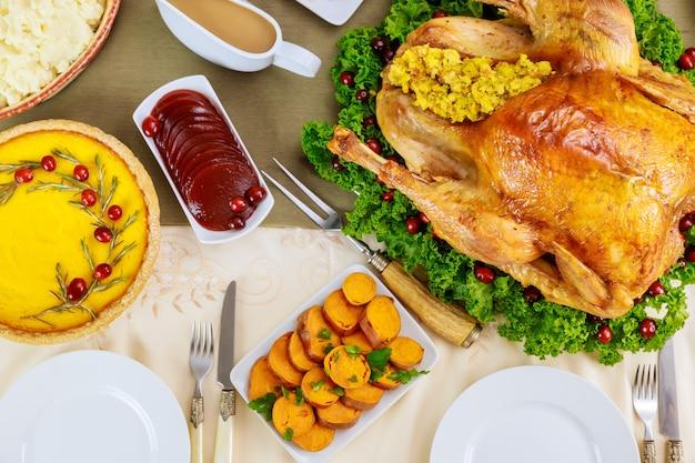 Mesa de natal servida com peru, decorada com couve e cranberry.