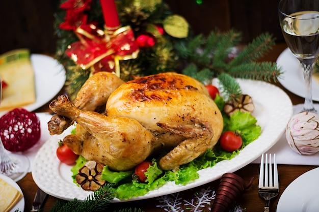 Mesa de natal servida com um peru, decorado com enfeites e velas brilhantes