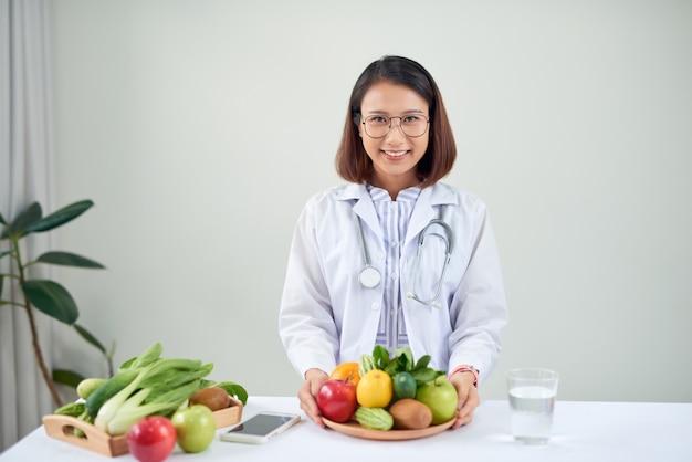 Mesa de nutricionista com frutas saudáveis, sucos e fita métrica. dietista trabalhando em plano de dieta no escritório, sorrindo para a câmera. perda de peso e conceito de nutrição certa
