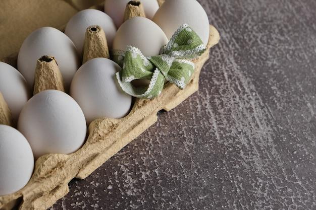 Mesa de páscoa definindo composição festiva. ovos brancos e um decorado em caixa de papelão na mesa cinza. copie o espaço do texto.
