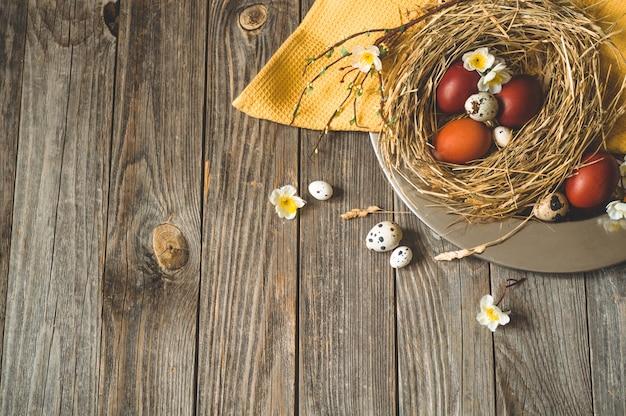Mesa de páscoa feliz ovos de páscoa em um ninho em uma placa de metal em uma mesa de madeira. feliz páscoa conceito