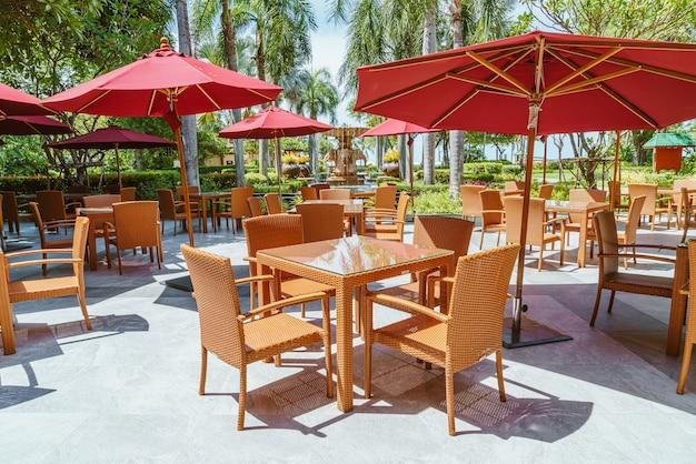 Mesa de pátio externo vazia e cadeira com guarda-chuva