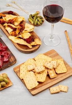 Mesa de petiscos com diferentes antepastos, charcutaria, petiscos e vinhos. salsichas, fiambre, tapas, azeitonas, queijos e bolachas para buffet. vista superior, configuração plana