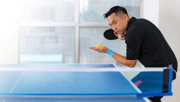 Mesa de ping pong, masculino jogando tênis de mesa com raquete e bola em um salão de esporte