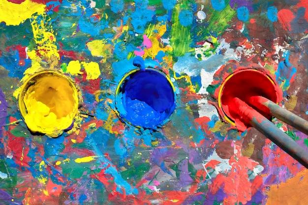 Mesa de pintura guache com manchas de tinta e copos com tintas amarelas, azuis e vermelhas